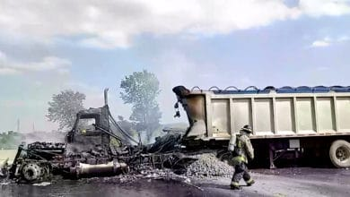 A firefighter walks by a burnt-out tractor-trailer on Ontario Highway 401 near toronto Canada