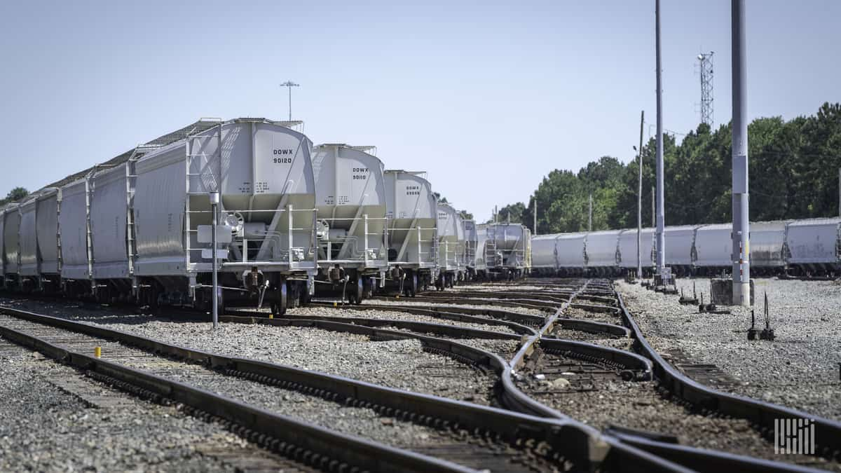 A photograph of a rail yard. There are several lines of trains parked at the yard.