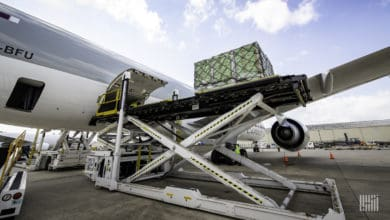 Machine lifts cargo pallets up to door of plane for loading.