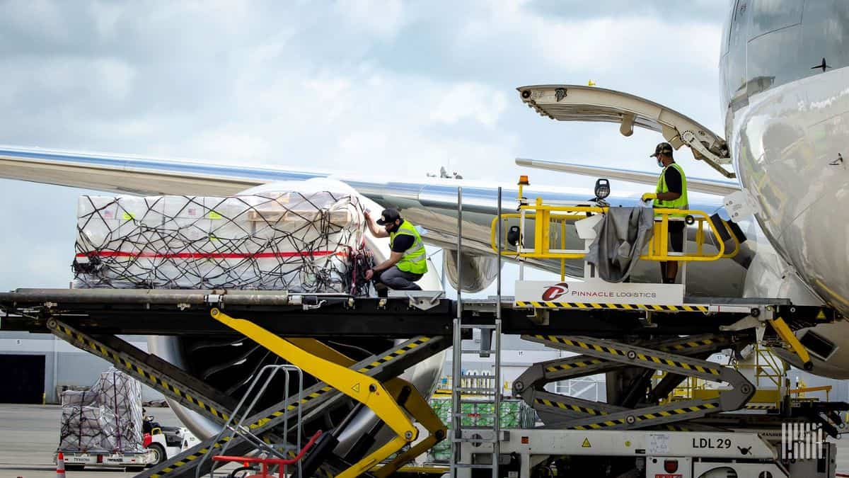 Cargo pallets on a lift platform being loaded in the side of a large plane. Airlines carried fewer loads in the first six months, but made more money because they could charge much more.