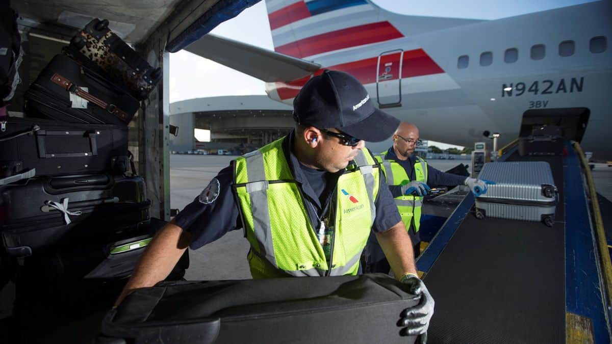 A baggage worker transfers bags from a cart to a conveyor belt for loading onto a plane. Ground workers at American Airlines are among thousands of employees who could lose their jobs.