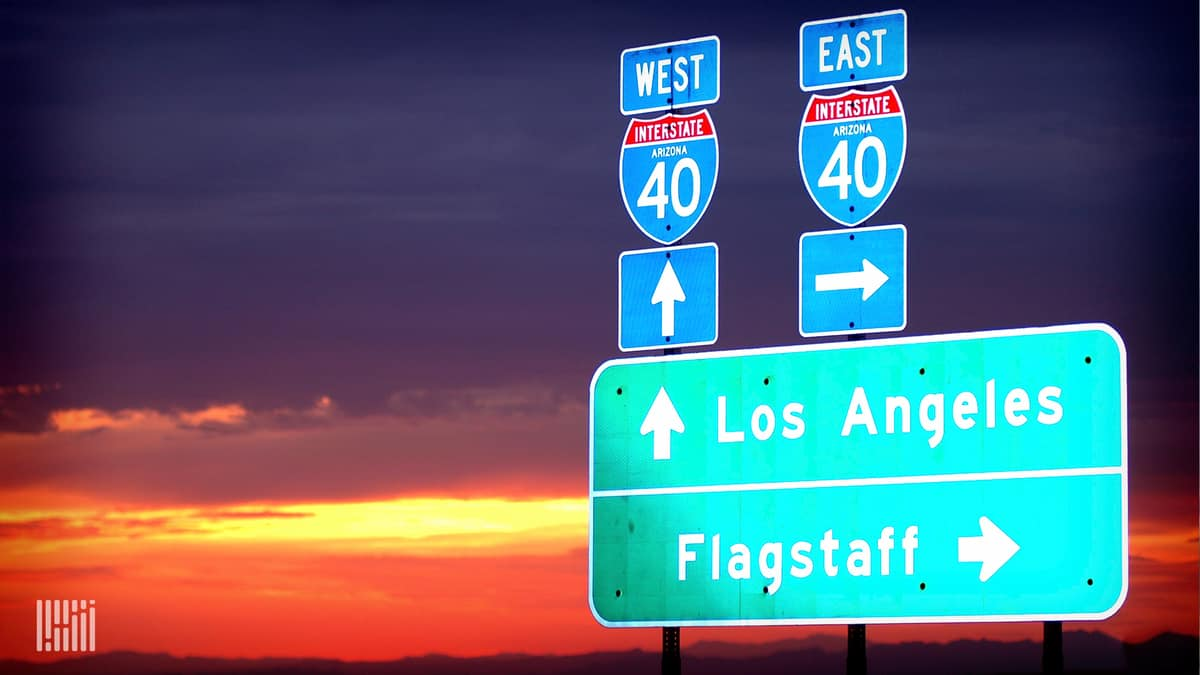 Interstate highway directional signs at sunset. (Photo: Jim Allen/FreightWaves)