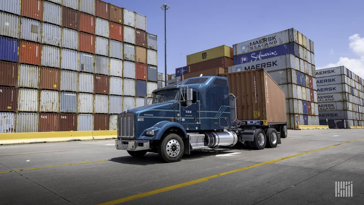 A tractor pulls a flatbed trailer carrying an intermodal container.
