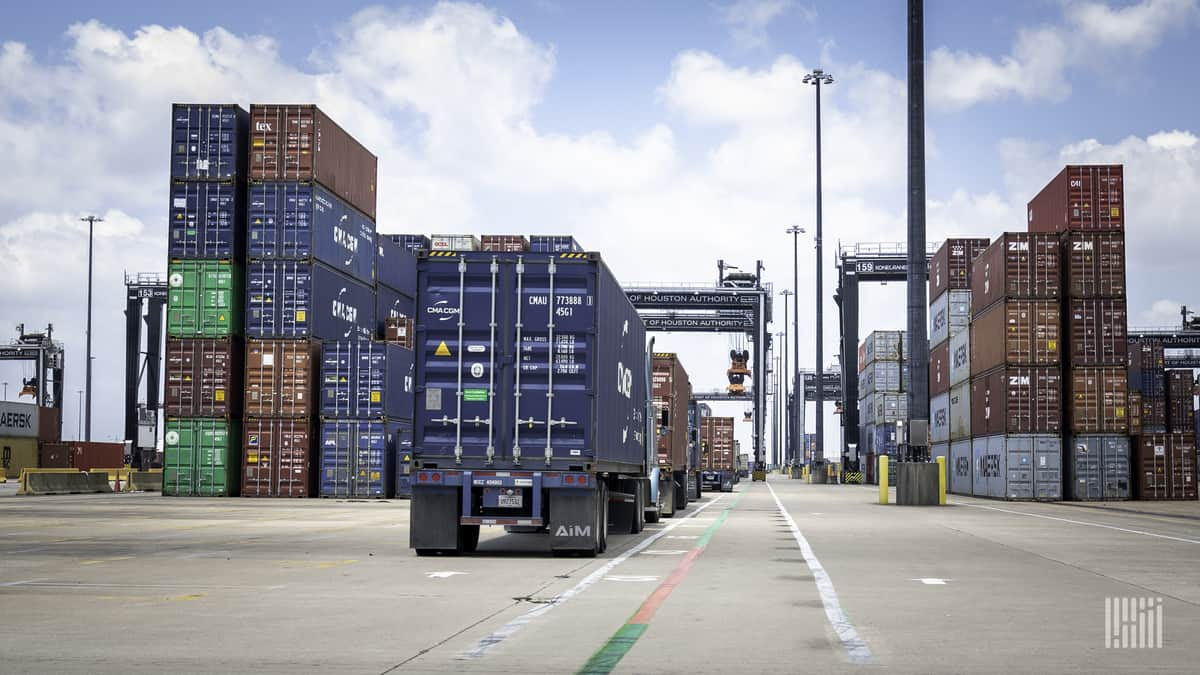 Trucks lined up between stacks of intermodal containers.