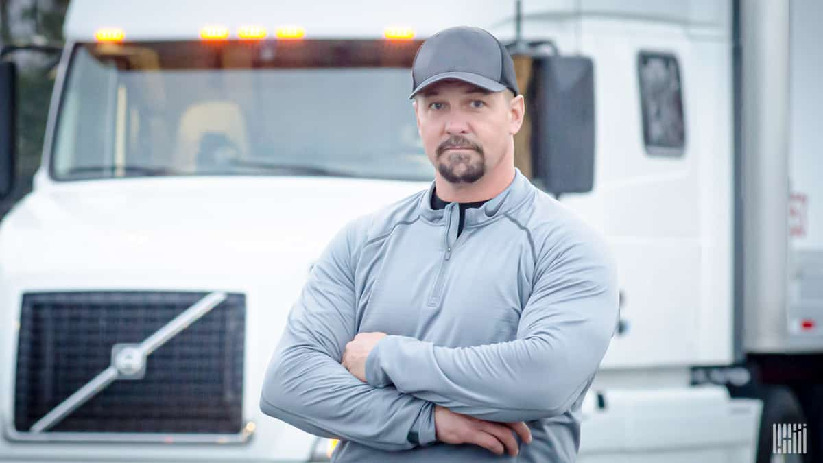 A driver stands in front of his rig. Where will his next load come from?