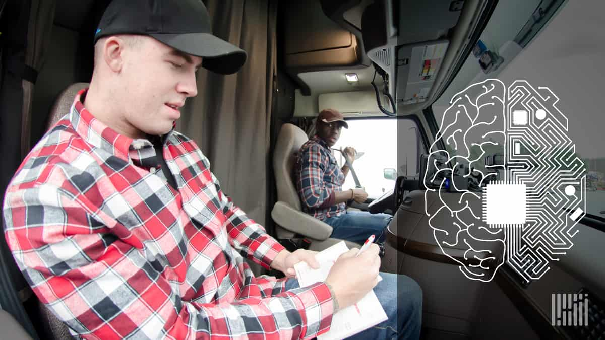 Two truck drivers working together in a truck cab.