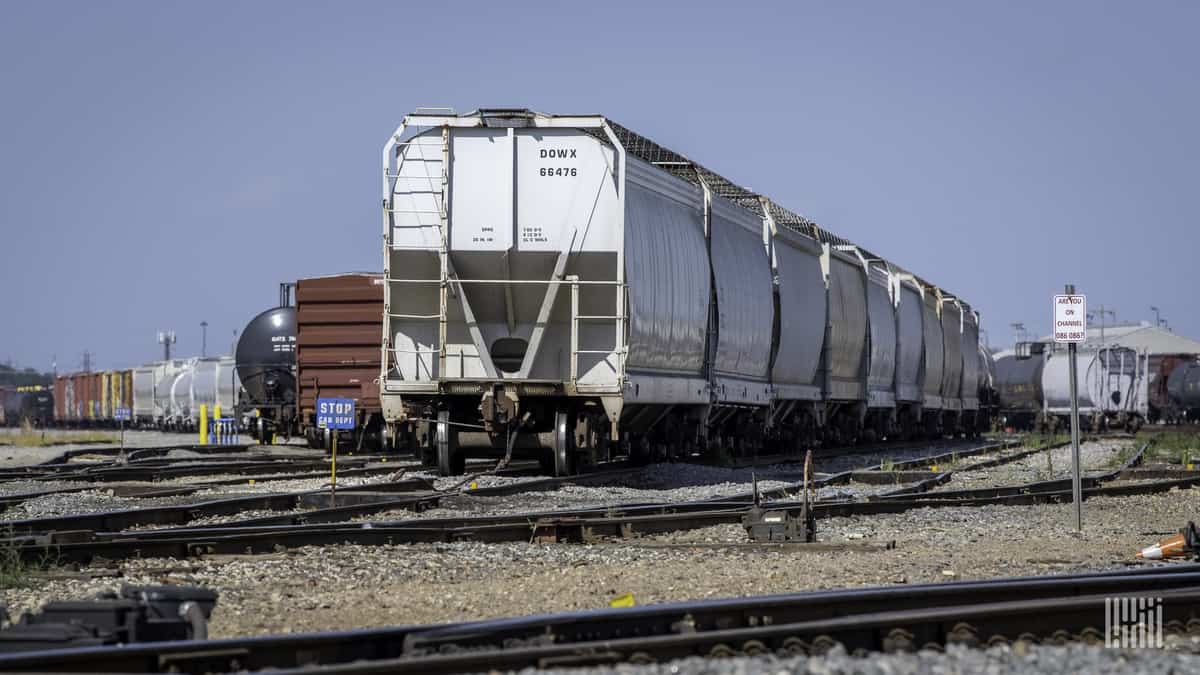 A photograph of a hopper car parked in a rail yard.