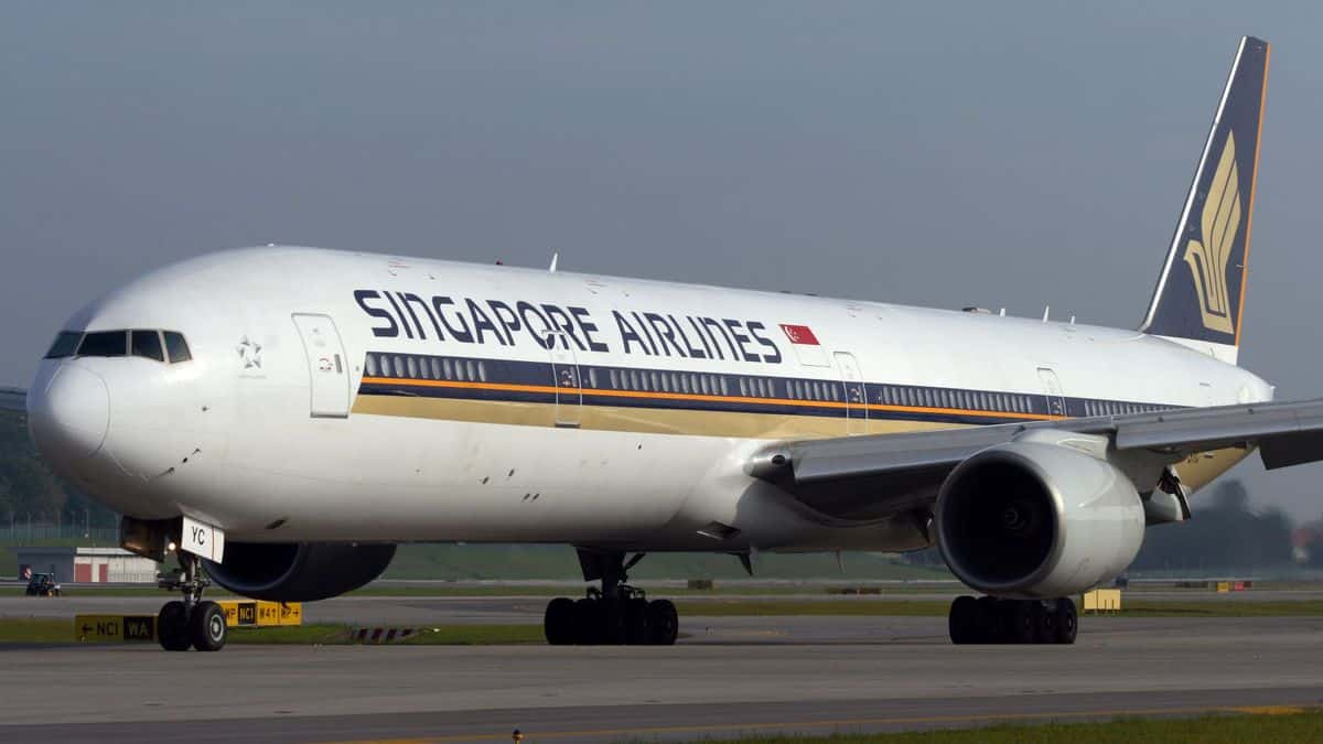 A big white Singapore Airlines plane, viewed at 45-degree angle from front as plane sits on ground.