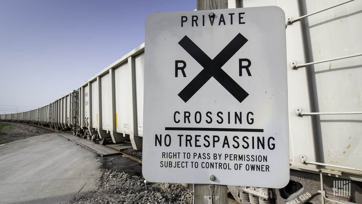 A line of hopper cars stretches into the distance at a private rail crossing.