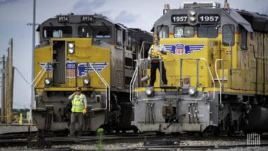 A photograph of two locomotive engines. Two men are standing in front of the locomotives.
