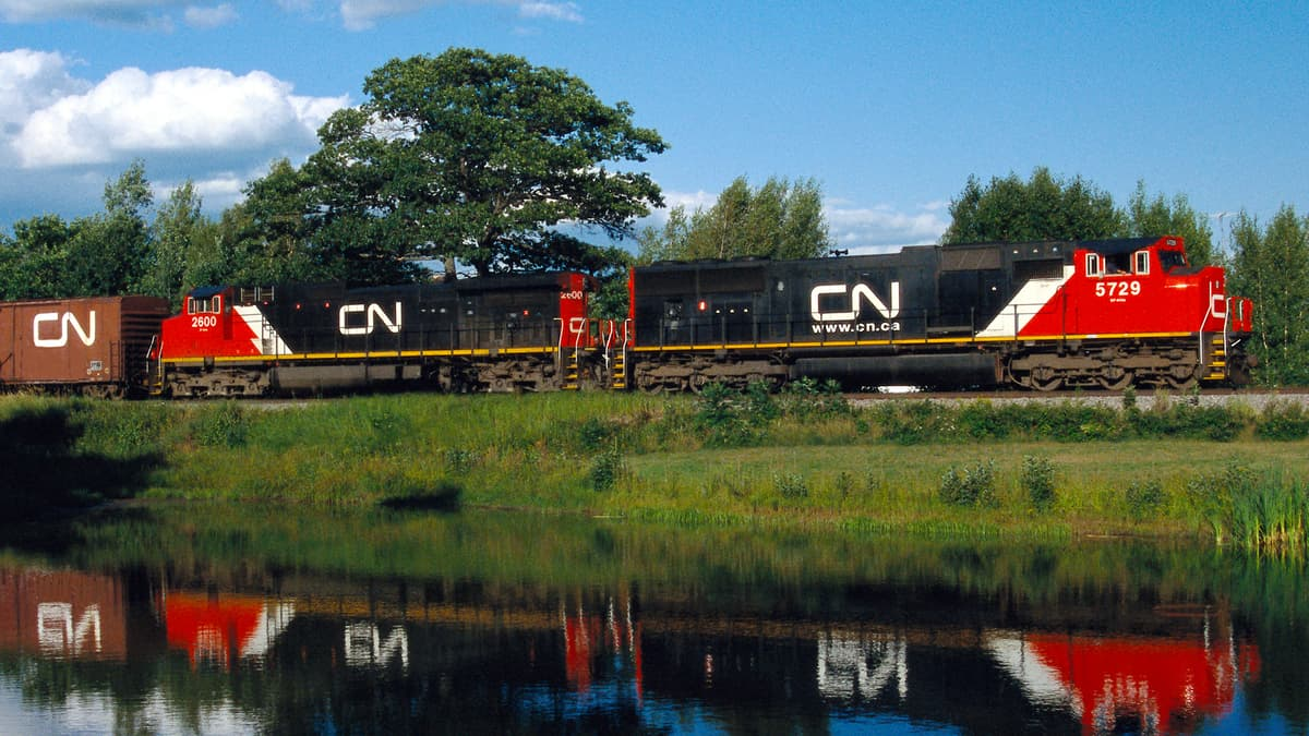 A photograph of a train traveling in a grassy field. A reflection of the train is on the water of a nearby pond.