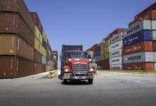 Red drayage truck loading container at port
