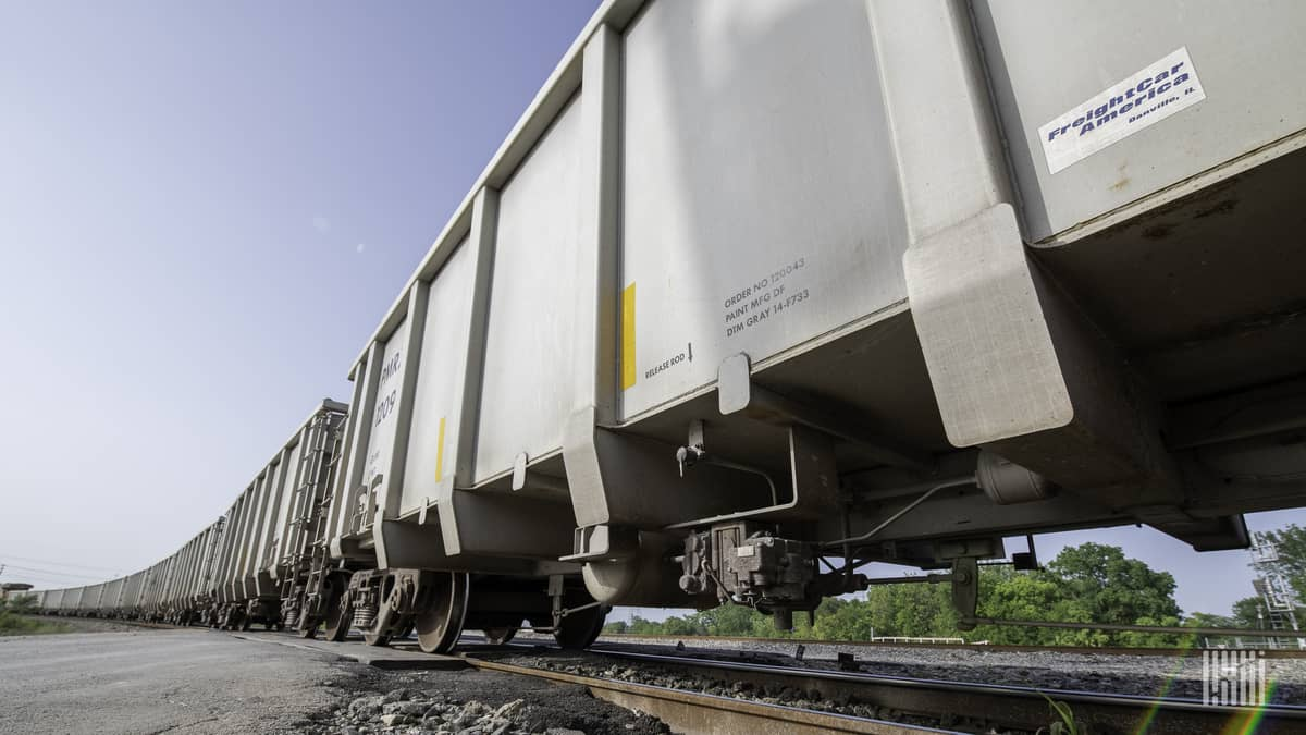 A photograph of a line of railcars parked in a rail yard.