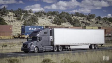 A photograph of a truck with a trailer and an intermodal train behind the truck.