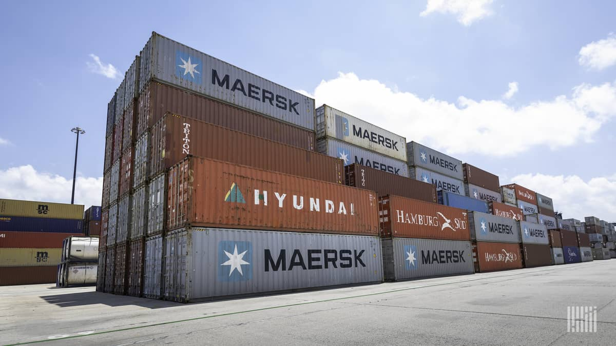 Containers rise five-high at a dockyard holding area.