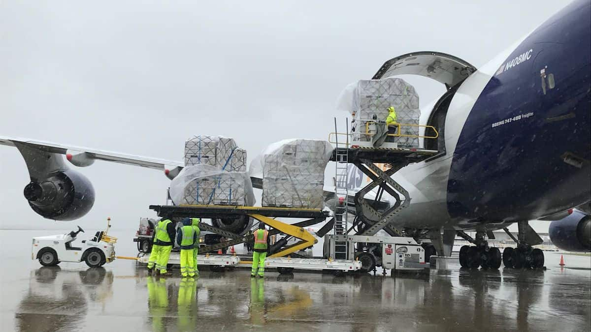Big cargo plane being unloaded in the rain at airport.