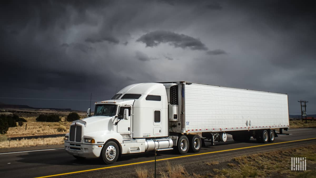 Tractor-trailer heading down highway with dark storm cloud in background.