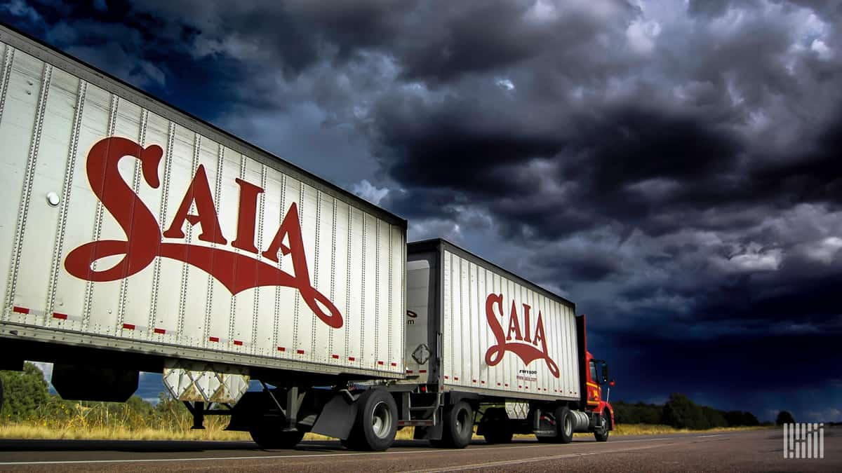 SAIA tractor-trailer heading down highway with dark storm cloud across the sky.