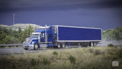 Tractor-trailer heading down highway with dark storm cloud in the background.