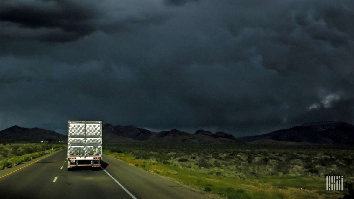 Tractor-trailer heading down highway with very dark storm cloud ahead.