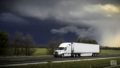 Tractor-trailer heading down a highway with dark storm cloud across the sky.