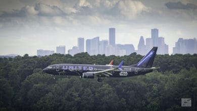 A dark blue United Airlines jet comes in for landing, side view right above the tree tops. United posted a $1.6 billion loss Tuesday.