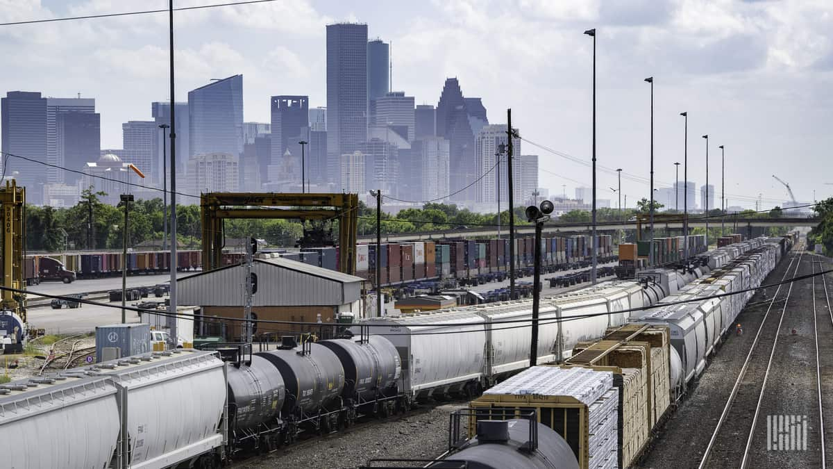 A photograph of rail yard. A city with skyscrapers is in the background.