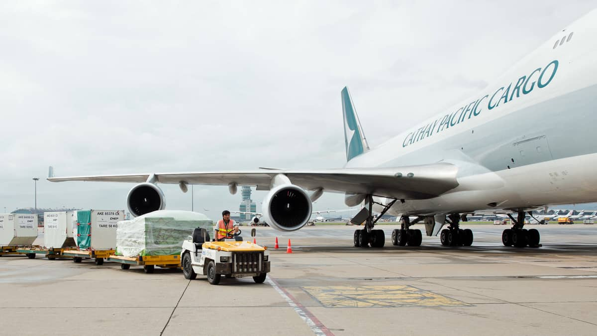 A cargo tug drops off a load next to a Cathay Pacific jet. The air cargo business in June was down a fifth from last year's level.