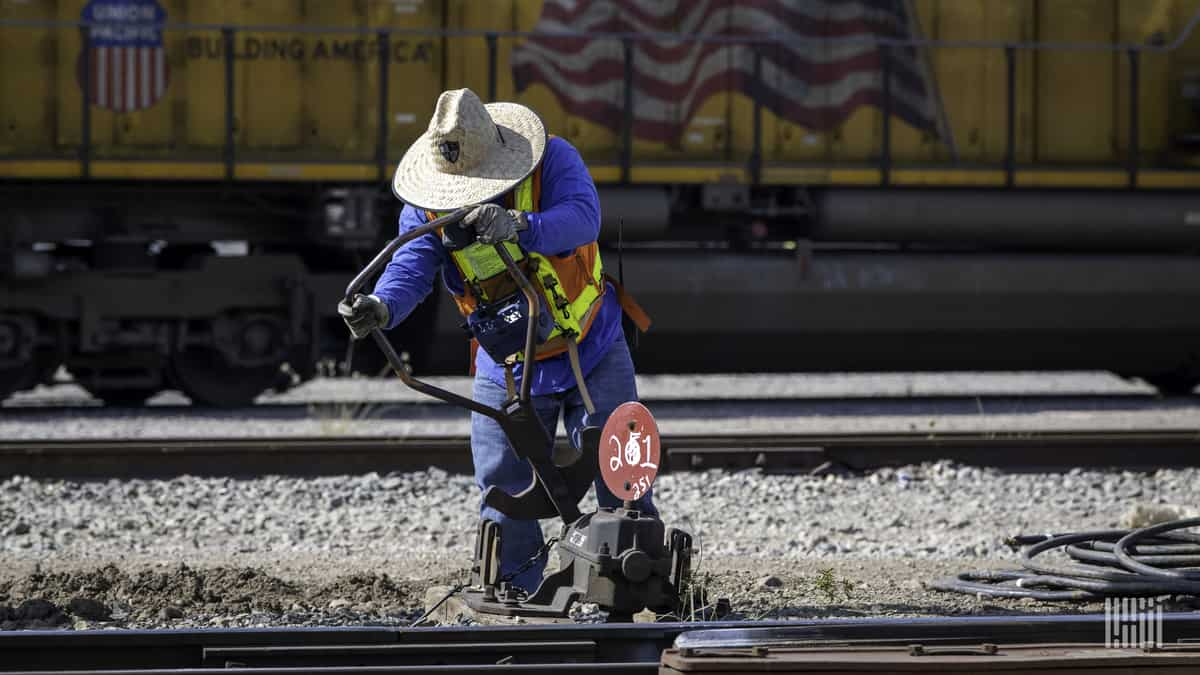 A photograph of a railroad employee and worker.