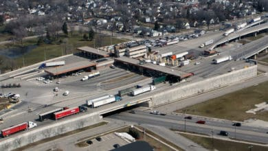 An aerial view of trucks at a U.S.-Canada border crossing. Truck crossings at the border have trended higher since April.