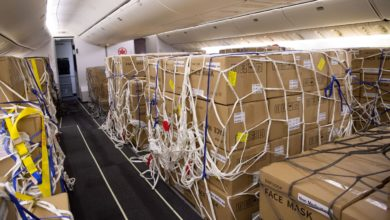 Boxes of face masks and tied down with nets on the passenger cabin floor of plane after seats were removed. Air Canada was faster than U.S. airlines to modify planes for this type of cargo operation.