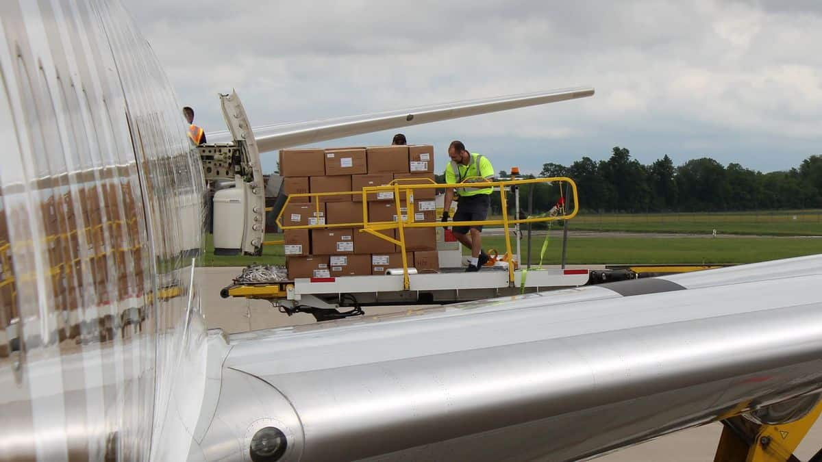 Pallets of freight offloaded an Emirates 777 passenger plane onto a hydraulic lift. The use of passenger planes as freighters is dictated by strong market economics.