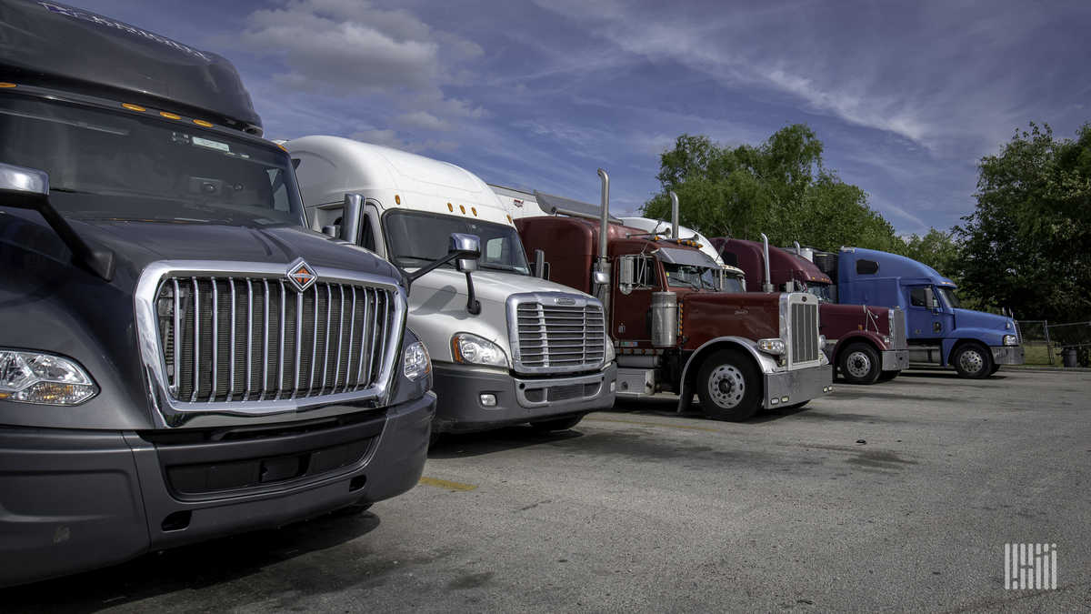 Different makes/models of Class 8 trucks in a parking lot.