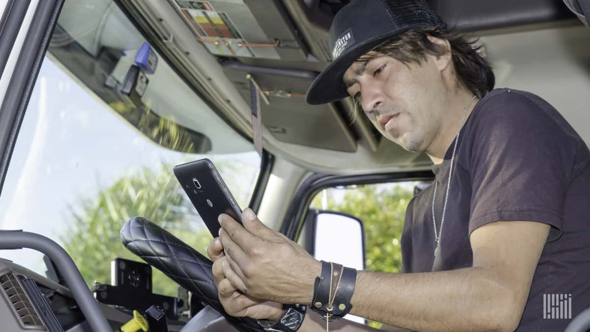 A driver checks a message about his next pick up on his smartphone.