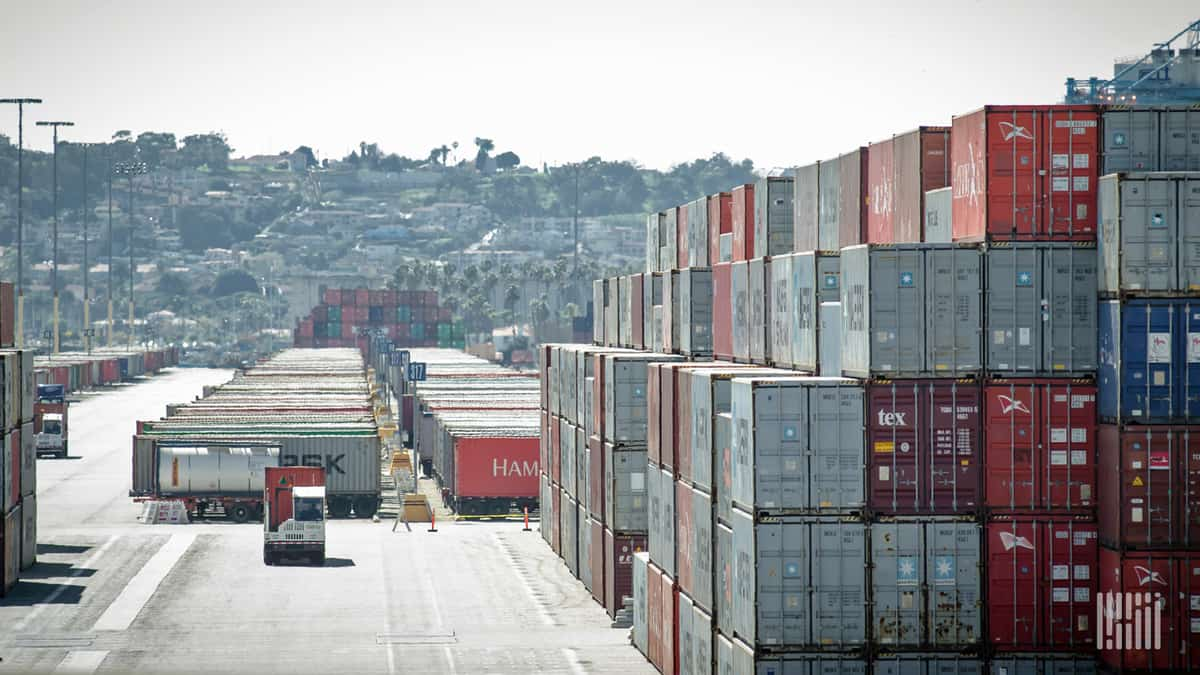In this photo, the stacks of containers look almost as high as the hills behind them.