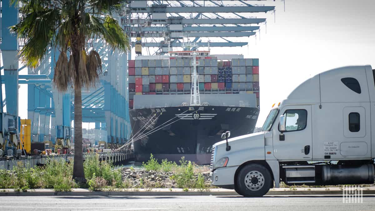A tractor waits near the docks while a ship is unloaded.