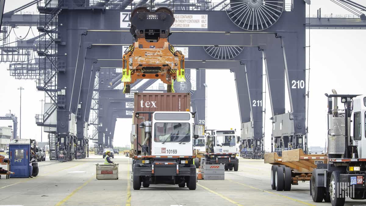 One of this port's cranes about to take a container from a drayage tractor.