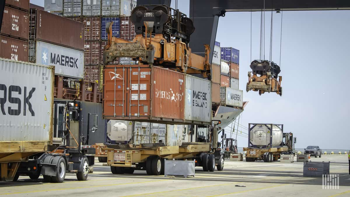 A port's crane removes containers from a flatbed.