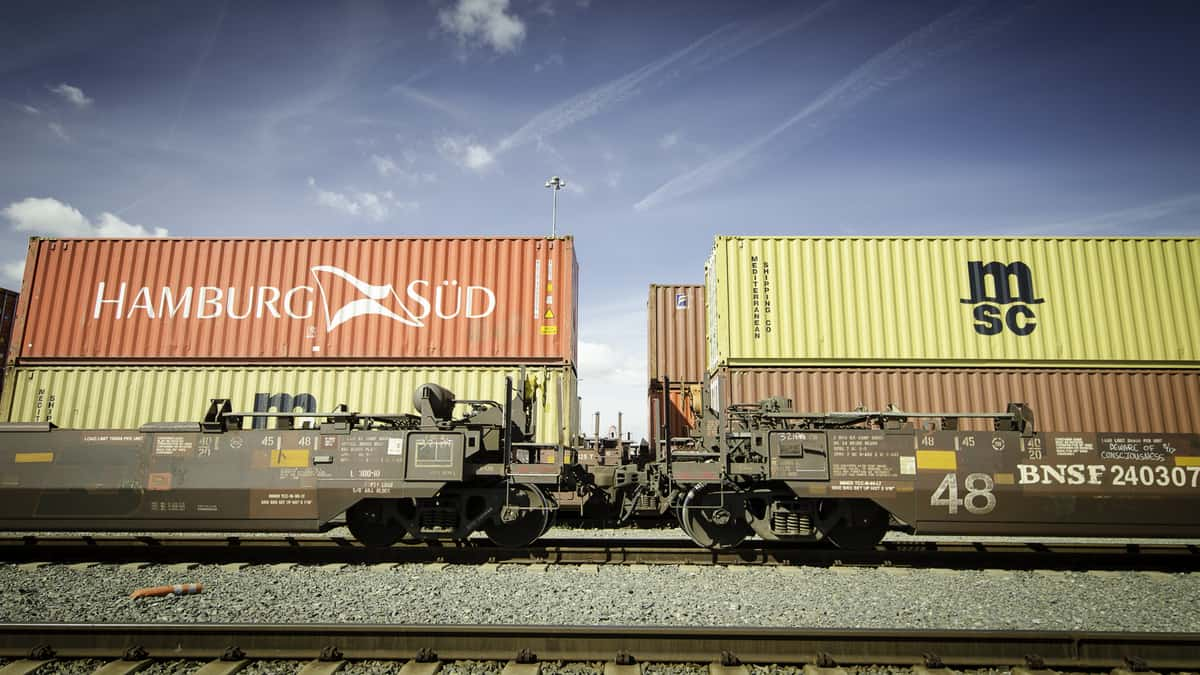 A photograph of a double-stacked intermodal train parked at a rail yard.