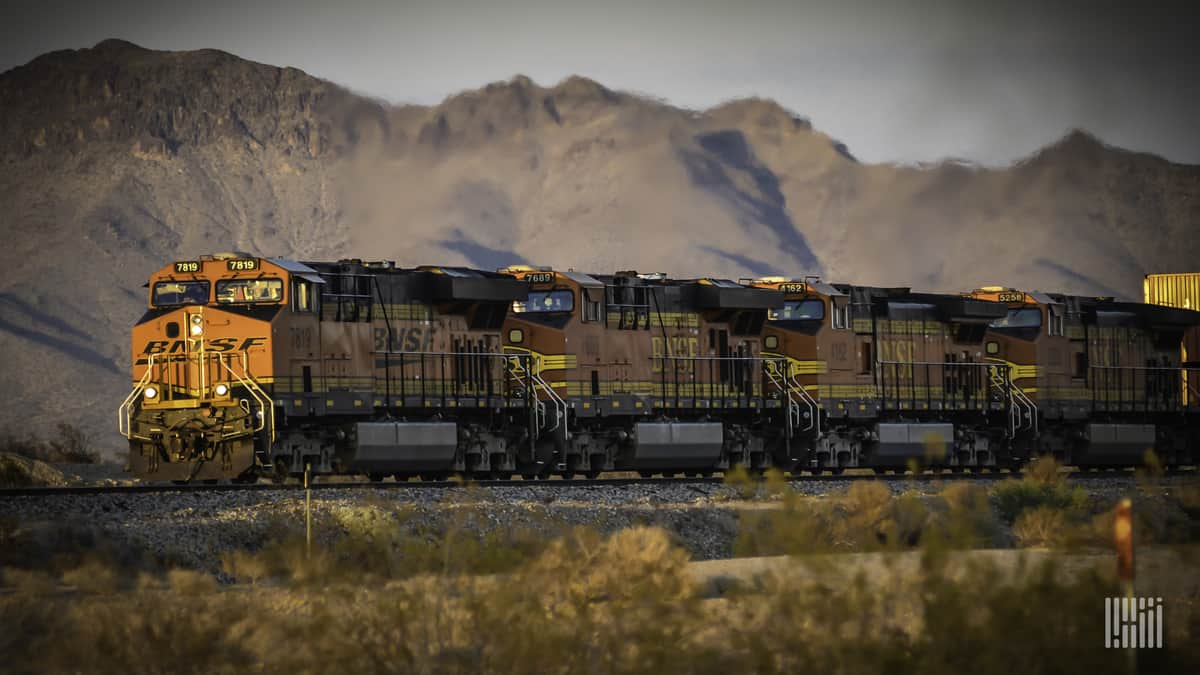 A photograph of a BNSF train traveling through an open field of dry land. A mountain range is in the background.