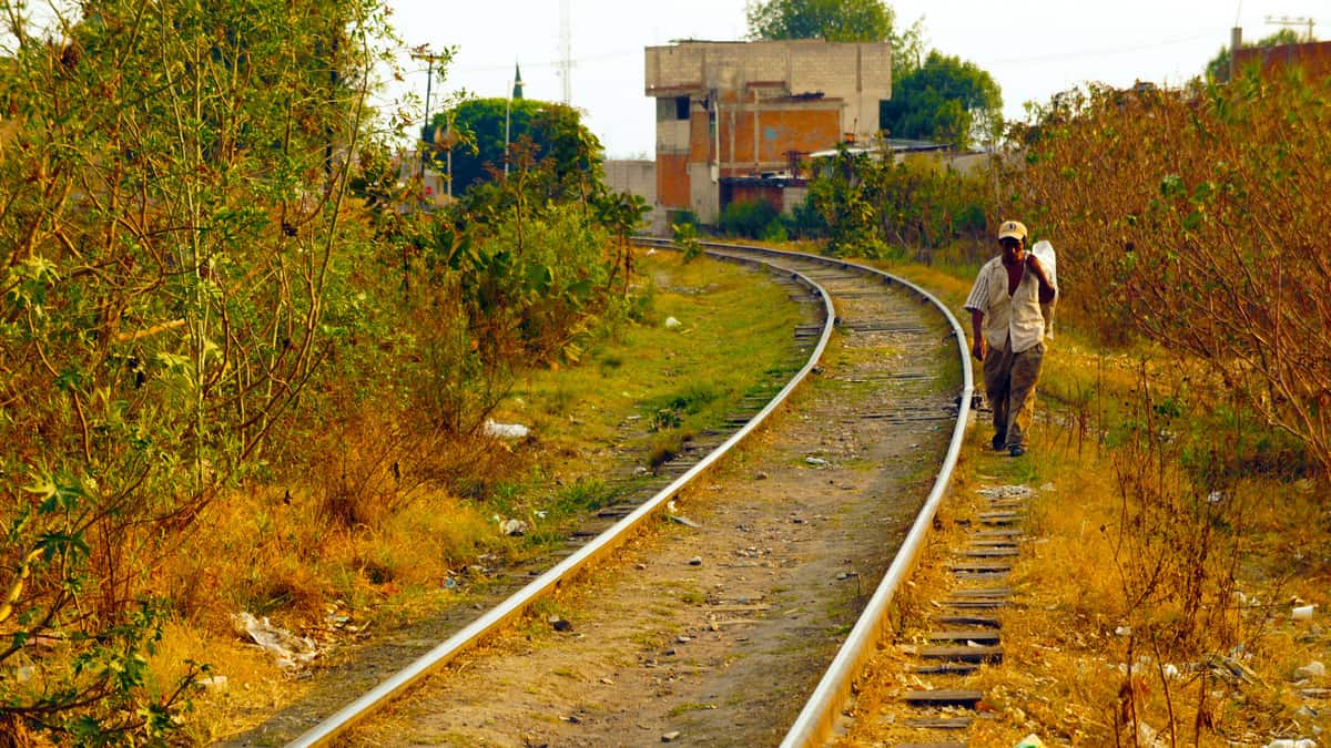 A man walks along railroad tracks in Mexico.