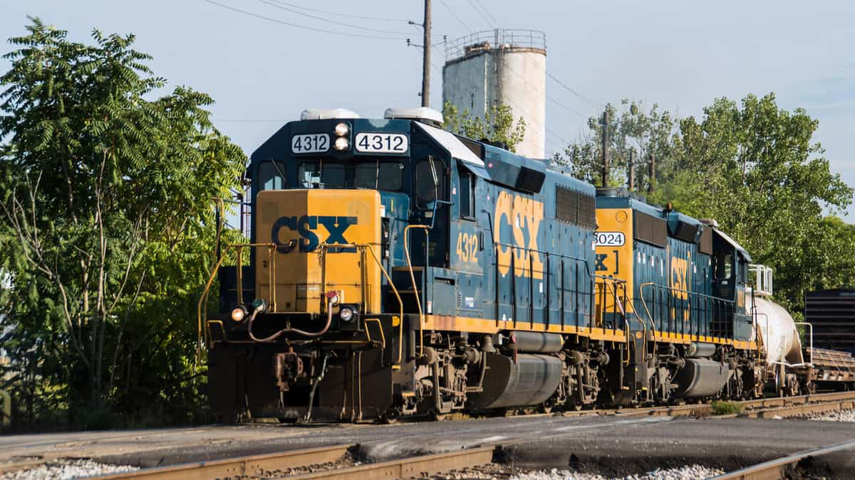 A photograph of a CSX train. There is a line of trees behind the train and alongside the train track.