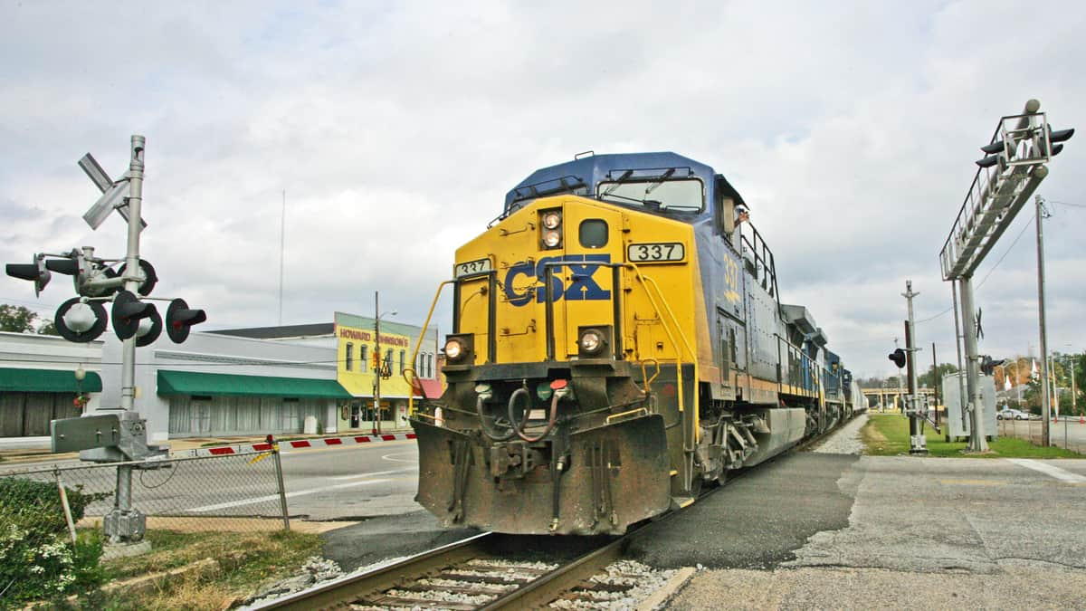 A photograph of a CSX train at a rail crossing. There are town buildings nearby the train tracks.