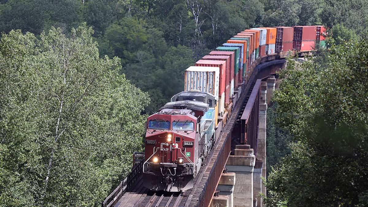 A photograph of a Canadian Pacific train carrying containers. The train is traveling through a forest.
