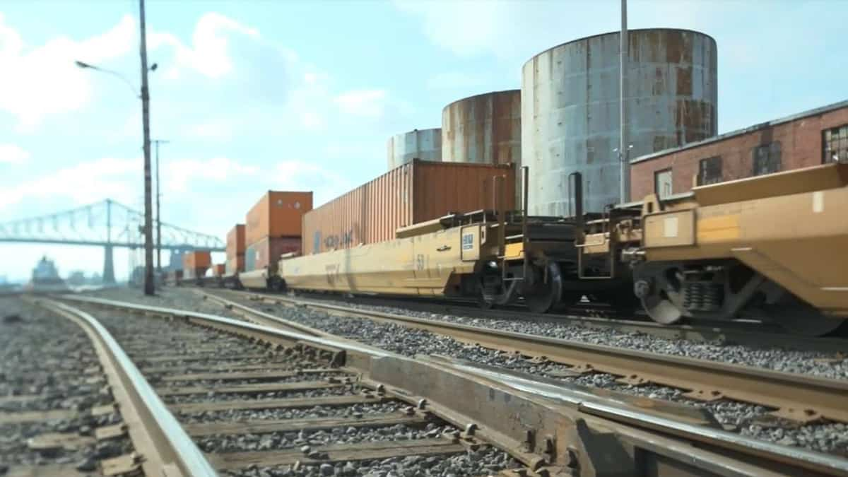 A photograph of a train with hauling intermodal containers at a rail yard.