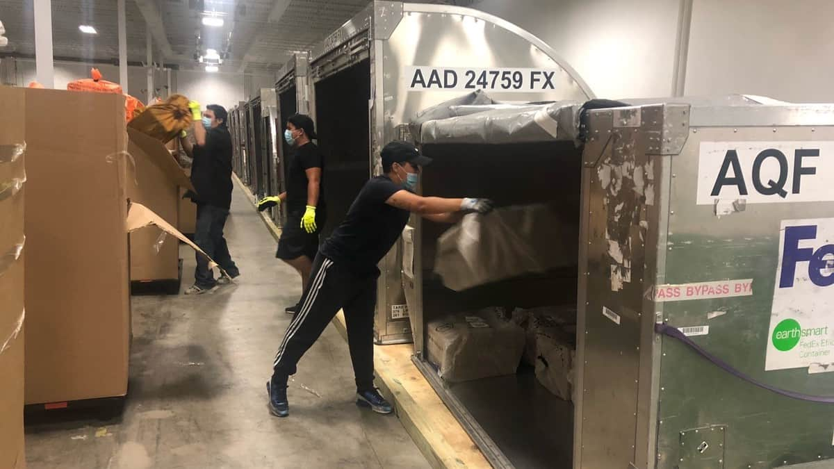 Warehouse workers unload metal containers filled with small mail envelopes and parcels that arrived by air. Cargo Force does sort and prep work for the USPS.