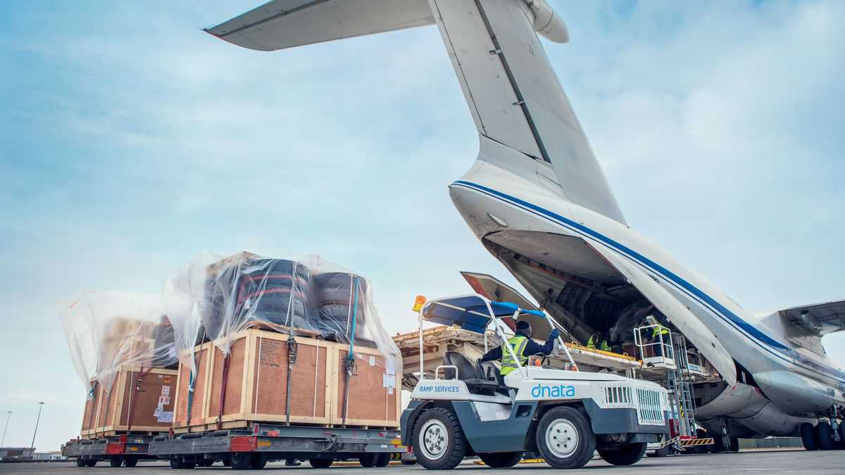 A white cargo tug moves a shipment after unloading from the rear ramp of a massive cargo plane. dnata is an airport services operator and faces congestion problems at Sydney Airport.