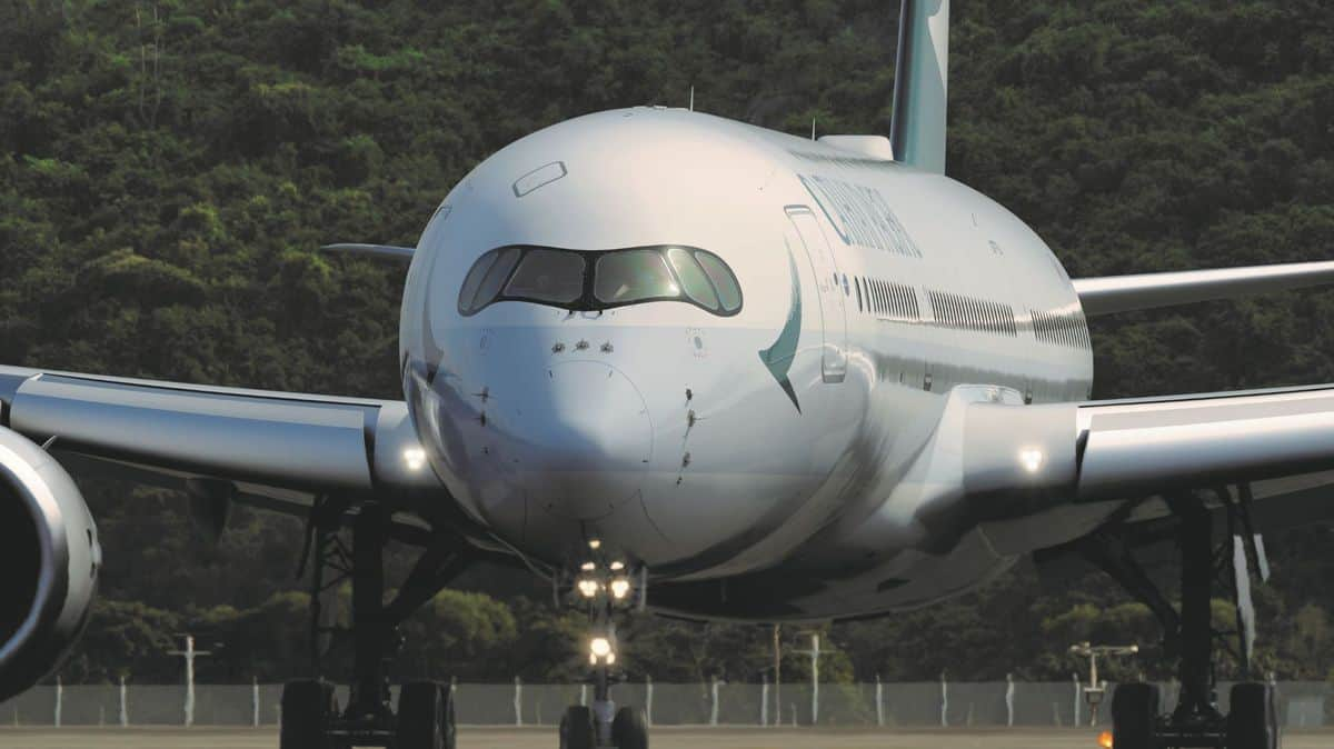 Staring straight ahead at a big white jet. from the front. Cathay Pacific is storing planes in sunny climates.