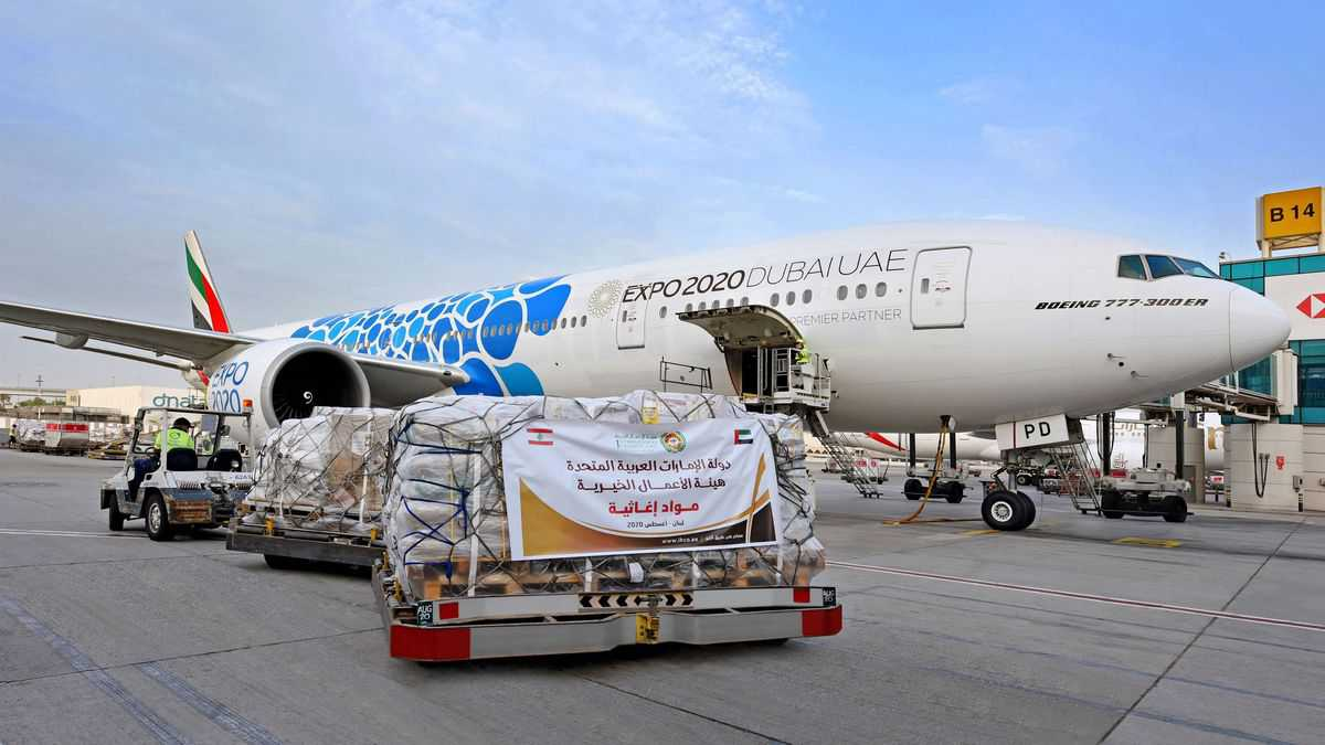 A pallet of emergency supplies with a sign in Arabic sitting on the tarmac next to an Emirates plane on a sunny day. Emirates is flying supplies to Beirut to help the city recover from the explosion.