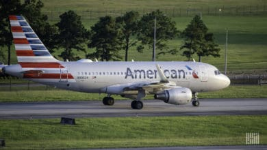 A silver American Airlines plane with red, white and blue striped tail rolls down taxiway. American plans to cut 19,000 jobs.